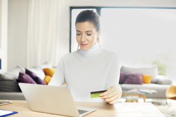 Shopping from home. Attractive woman using her laptop to make online purchases with her credit card while sitting at desk at home.