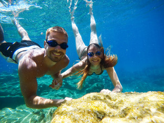 Underwater photo of young cute romantic love couple exploring and enjoying with goggles in the exotic turquoise sea near the coral reef while holding hands together.