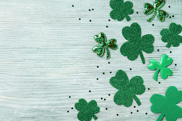 Saint Patricks Day background with green shamrock on white rustic board top view.
