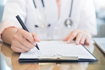 female doctor writing something on clipboard.