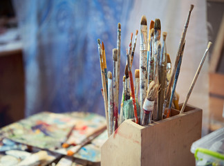 Many different used brushes for painting with oil paint, in the artist's workshop