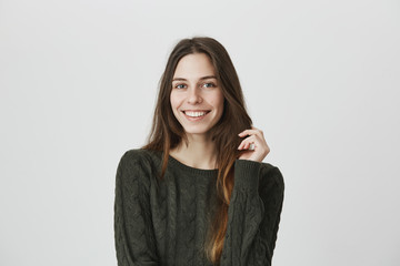 Beautiful young female with long dark hair in casual clothes smiling joyfully at camera, being pleased to hear compliments, isolated against blank wall background. Attractive european student girl