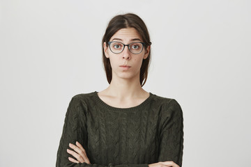 Portrait of smart attractive young woman with crossed hands in dark-green sweater and glasses with confident and smug expression over white background. No I don't want to share my lecture notes