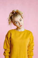 close-up portrait of cheerful  young caucasian female with curly blonde hair, in yellow sweater poses on a pink background.