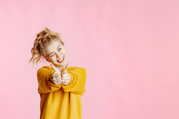 close-up portrait of cheerful  young caucasian female with curly blonde hair, in yellow sweater poses on a pink background. Woman showing Ok gesture and smiling.