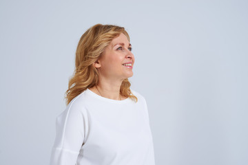 Mature blond woman looking at something good and smiling