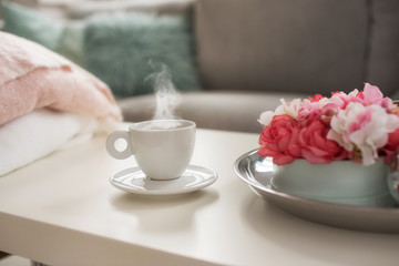 Still life details in home interior of living room. Sweaters and cup of coffe with steam on a serving tray on a coffee table. Breakfast over sofa in morning sunlight.
