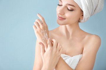 Young woman applying hand cream on color background