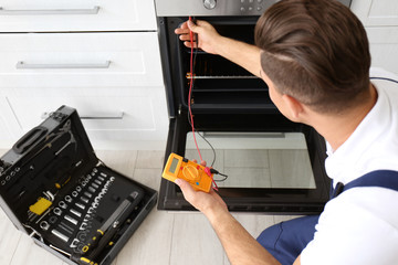 Young man with multimeter repairing oven in kitchen