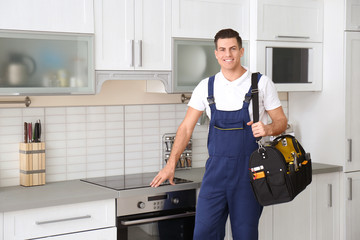 Young worker with tool bag standing near oven in kitchen