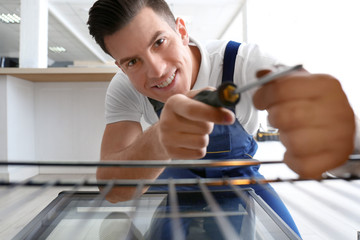 Young man repairing oven, view from inside