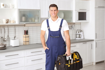 Young worker with tool bag standing in kitchen