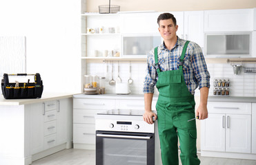 Young worker standing near oven in kitchen