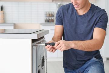 Young man repairing oven, closeup