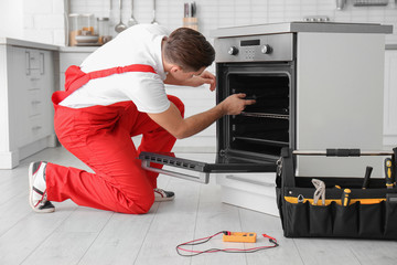 Young man repairing oven in kitchen
