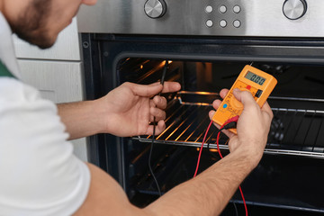 Young man with multimeter repairing oven, closeup