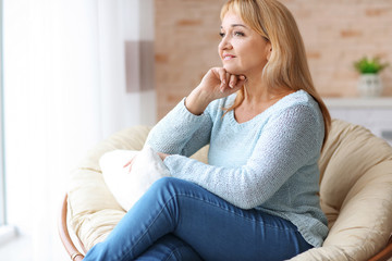 Happy mature woman relaxing in armchair at home