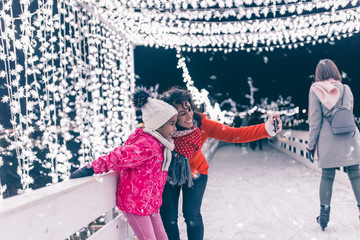 Cute black girl taking selfie photo with her mother at ice skating.