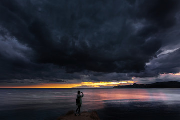 girl at the sea in the evening takes pictures of the sunset before the storm