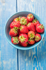 Ripe red strawberries in white bowl.