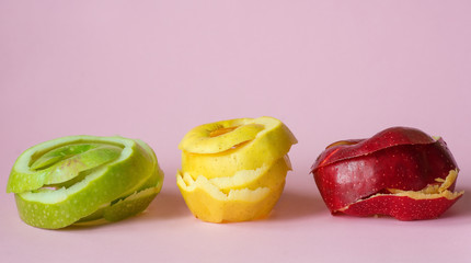 red, green, yellow apple peels on pink background as a symbol of recycling circulate economy
