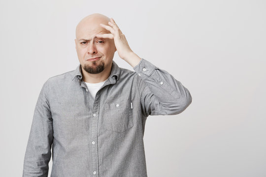 Stressed frustrated caucasian bearded bald male dressed in gray shirt touching forehead with hand, suffering from pain, being tired and overworked. Hairless man frowning face in irritation and pain