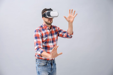 Man with virtual reality headset on grey background