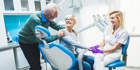 Senior couple having dental treatment at dentist's office.