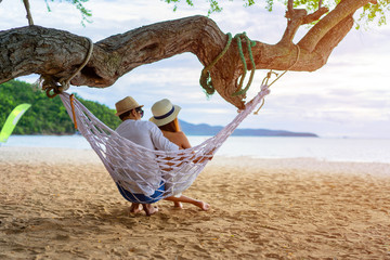 couple lover enjoy honeymoon and long vacation on the sea beach, siiting on the swing together relax and confortable, valentine occasion