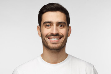 Close up portrait of smiling handsome man in white t-shirt isolated on grey background