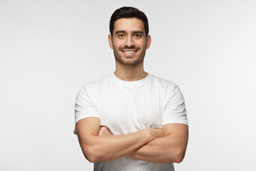 Portrait of smiling handsome man in white tshirt standing with crossed arms isolated on grey background