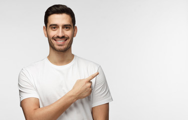 Attractive young man in white t-shirt pointing right with his finger isolated on gray background