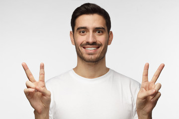 Indoor portrait of young male isolated on gray background in white tshirt with optimistic smile, showing victory sign with both hands, looking friendly and willing to welcome and communicate