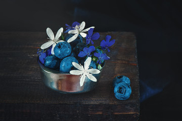 Ripe blue blueberries in a metal Cup with tiny white and blue flowers of clematis. The rustic style. Copy space.