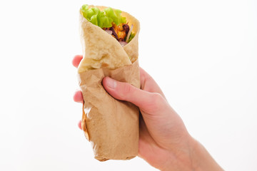 Mexican burrito in hand with chicken, pepper and beans