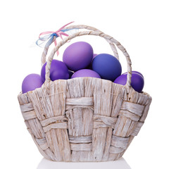 Basket full of eggs colored in shades of violet isolated on white background