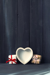 White heart with gifts. Dark wooden background. Copy space. St. Valentine's Day.