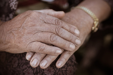 Hands Asian elderly woman grasps her hand on lap, pair of elderly wrinkled hands and Traces of hard work, World Kindness older and Adult care  concept. Senior citizen is common euphemism