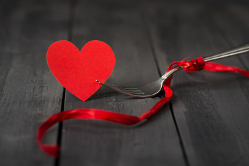 Red paper hearts and a fork with a ribbon. Dark wooden background. Copy space. St. Valentine's Day.