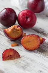 group of ripe plums with cut piece on white rustic table