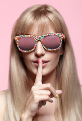 Young blonde woman with fun candy glasses and finger on lips on pink background