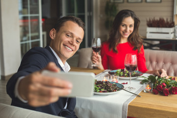 Young couple having romantic dinner in the restaurant taking selfie pictures