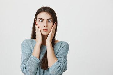 Indoor shot of pretty brunette woman making grimace with slanting blue eyes, touching her cheeks with hands, having tired and annoyed expression. Face expression and negative emotions