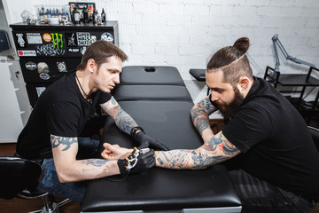 master tattooist makes a tattoo on the skin of the client with special equipment