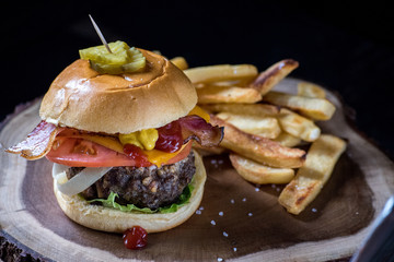 classic hamburger with tomato, lettuce, cheese, and pickles with fries