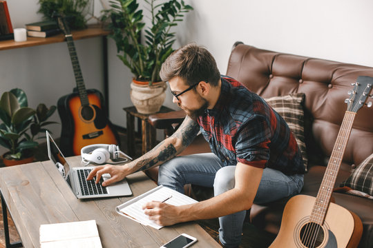 Young guitarist hipster at home with guitar browsing laptop writing