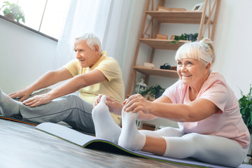 Senior couple doing yoga together at home health care legs stretching