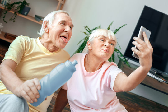 Senior couple exercise together at home health care selfie photos grimase