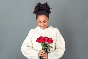 Young african woman isolated on grey wall studio winter concept red roses bouquet