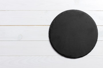 Round slate stand board a wooden background. space for text